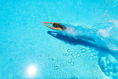 Woman diving underwater in swimming pool - p300m1166009 by Scott Masterton