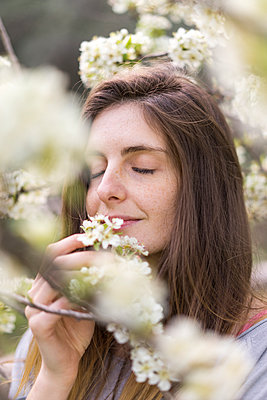 Portrait of woman smelling white blossoms of fruit tree - p300m1581662 by VITTA GALLERY