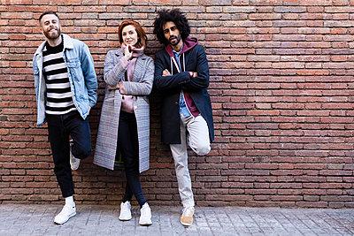 Portrait of three friends standing at a brick wall - p300m2083396 by Josep Rovirosa