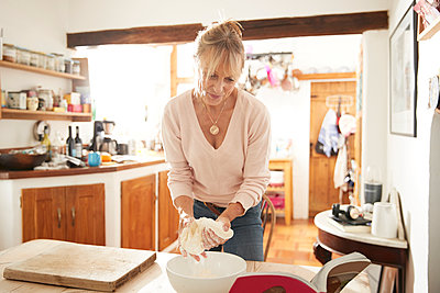 Smiling senior woman kneading dough while standing in kitchen at home - p300m2226435 by Pete Muller