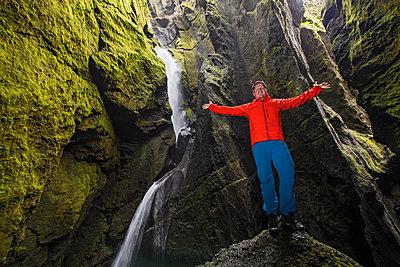 Man standing on rock, Stakkholtsgja Canyon, Thorsmork Valley, Hella, Rangarvallasysla, Iceland - p429m2036657 by Henn Photography