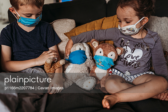 Young girl and young boy with masks playing with animals on couch - p1166m2207784 by Cavan Images