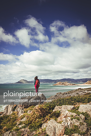 Dark-haired woman with red backpack, watching the sea from a cliff - p1166m2269588 by Cavan Images