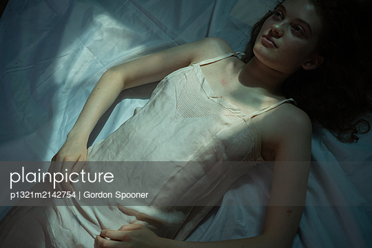 Woman lying on bed - p1321m2142754 by Gordon Spooner