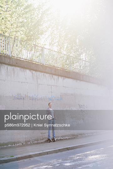 Junge Frau auf Rollschuhen steht vor einer Mauer - p586m972952 von Kniel Synnatzschke