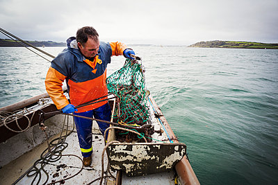 Traditional Sustainable Oyster Fishing. A fisherman opening a fishing creel on a boat deck.  - p1100m1216018 by Mint Images