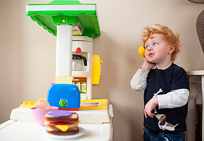 Toddler boy answering phone in his play kitchen with cute expression - p1166m2136716 by Cavan Images