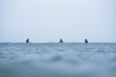 Women in a surf lineup during winter snow - p1166m2177149 by Cavan Images