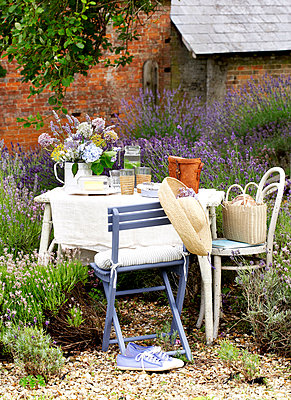 Blue chair with sunhat at table in walled garden;  Isle of Wight;  UK - p349m920076 by Rachel Whiting