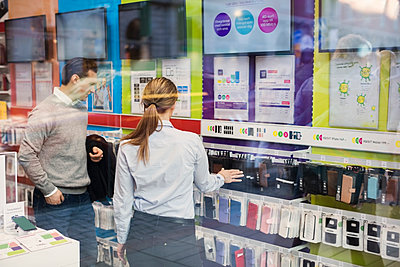 Saleswoman helping customer in buying phone cover seen through glass - p426m1147975 by Maskot