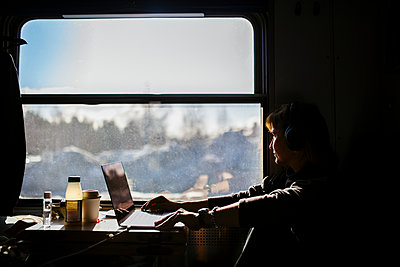 Female entrepreneur looking through window while traveling in train - p426m2279918 by Maskot