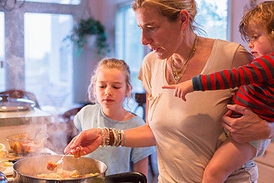 Caucasian mother and children cooking in kitchen - p555m1412252 by Marc Romanelli