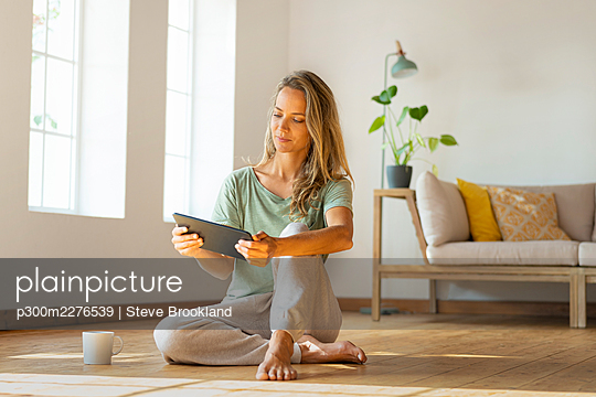 Woman in loungewear looking at digital tablet while sitting in living room - p300m2276539 by Steve Brookland