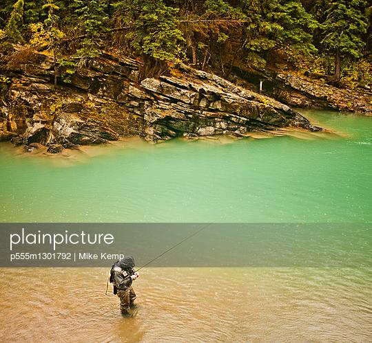 Caucasian man fishing in river - p555m1301792 by Mike Kemp
