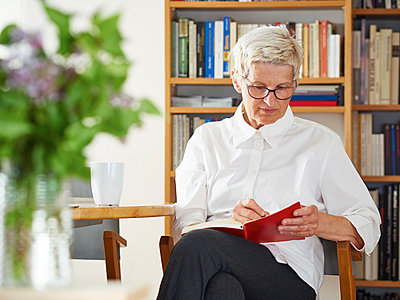 Senior woman writing in her notebook at home - p300m1153635 by Dieter Schewig