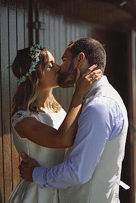 Kissing bridal couple in front of a beach hut - p300m2059028 von Javier Sánchez Mingorance