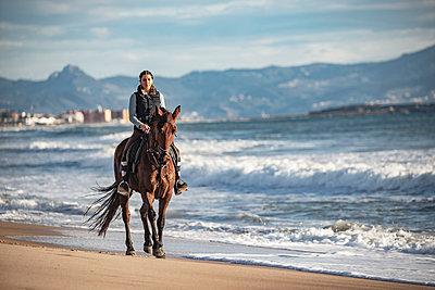 Spain, Tarifa, woman riding horse on the beach - p300m2080668 by Sebastian Kanzler
