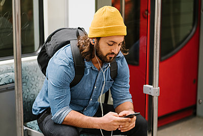 Man with backpack listening music with smartphone and earphones in commuter line, Berlin, Germany - p300m2143387 by Hernandez and Sorokina