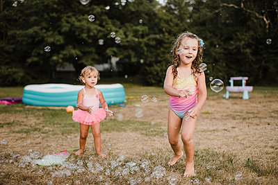 Two happy girls playing with soap bubbles in garden - p300m2206982 by Sara Monika