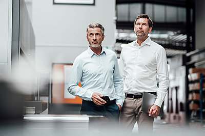 Businessmen looking away while standing by machinery in industry - p300m2225921 by Joseffson