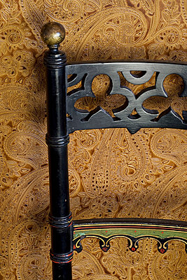 Carved black chair back and brown patterned wallpaper - p3493458 by Robert Sanderson