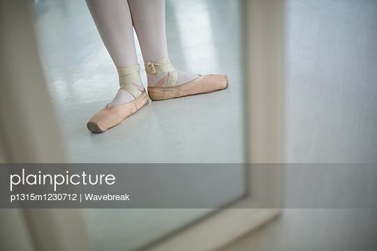Reflection of ballerinas feet wearing ballet shoes - p1315m1230712 by Wavebreak