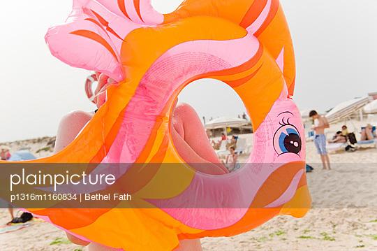 Kind bläst einen Schwimmreifen am Strand auf, Algarve, Portugal - p1316m1160834 von Bethel Fath
