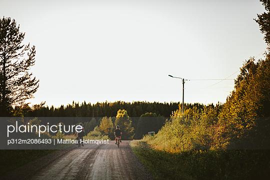 Boys riding bike on dirt track - p312m2086493 by Matilda Holmqvist