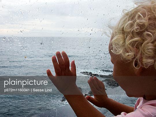 Mädchen blickt durch ein Fenster aufs Meer - p972m1160341 von Sesse Lind