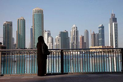 United Arab Emirates, Dubai, Arab Woman in a Hijab Walking background Skyline                                                                                                                            - p1014m806540 by Angelo Cavalli