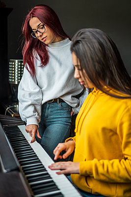 Two teenage girls practicing piano - p300m2166717 by Javier De La Torre Sebastian