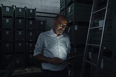 Businessman using tablet in a factory in the dark - p300m2170440 by Kniel Synnatzschke