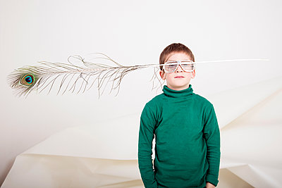 Boy with eyeglasses and peacock feather - p619m2178705 by Samira Schulz