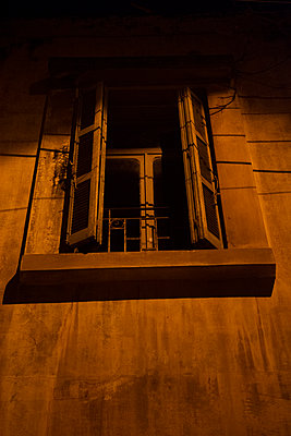 Old window with open shutters at night  - p794m2089183 by Mohamad Itani
