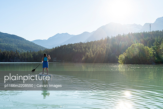 Barefoot woman in dress and life vest riding paddle board on calm lake water on sunny summer day in mountains in British Columbia, Canada - p1166m2208550 by Cavan Images