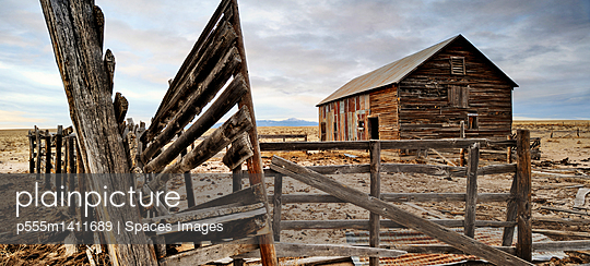 Close up of dilapidated fence and barn on abandoned farm - p555m1411689 by Spaces Images