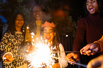Playful girl with sparkler celebrating with family - p1023m1575870 by Sam Edwards