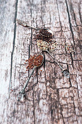 Three old tea spoons of different sorts of quinoa on wood - p300m1176162 by Mandy Reschke