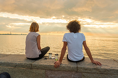 Rear view of couple sitting on retaining wall by sea against cloudy sky during sunset - p300m2132542 by A. Tamboly