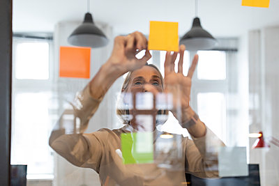 Mature businesswoman with adhesive notes on glass pane in office - p300m2154933 by Gustafsson