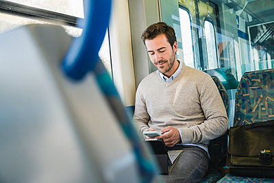 Young man using smartphone and tablet on a train - p300m2156735 by Uwe Umstätter