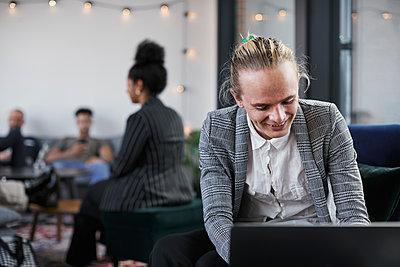 Man in modern office using laptop - p312m2299505 by Plattform