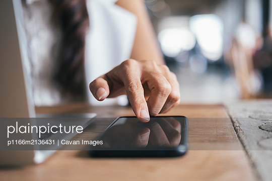 Close up woman hand press on mobile phone. - p1166m2136431 by Cavan Images