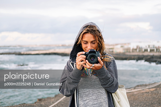 Young woman taking picture with camera while standing on beach - p300m2225248 by Daniel González