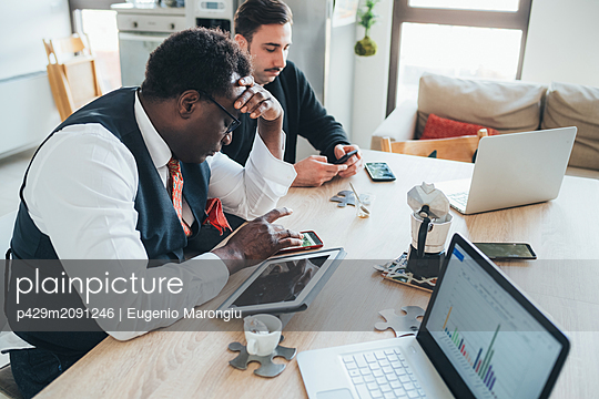 Businessmen using smartphone in loft office - p429m2091246 by Eugenio Marongiu