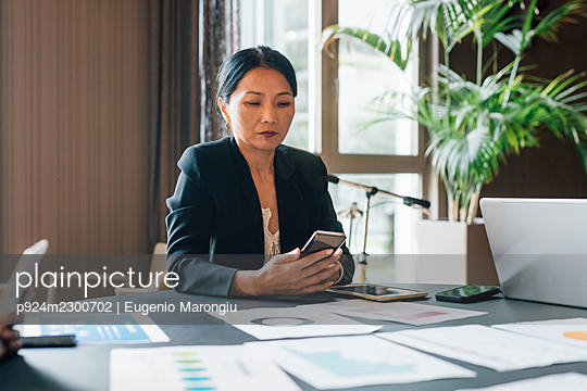 Italy, Businesswoman using smart phone at table in creative studio - p924m2300702 by Eugenio Marongiu