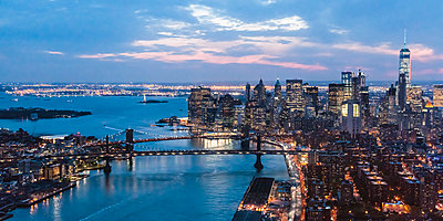 High angle view of Brooklyn and Manhattan bridges over East river by illuminated cityscape at dusk - p1166m1230523 by Cavan Images