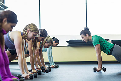 Instructor guiding women in doing push-ups with dumbbells at gym - p1166m1417398 by Cavan Images