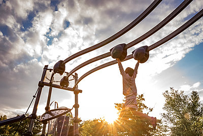 young girl swings from a moving monkey bar at a playground - p1166m2214625 by Cavan Images
