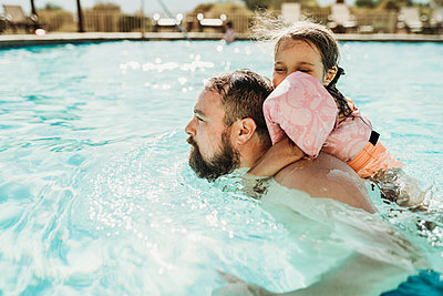 Father and daughter swimming together in a pool on California vacation - p1166m2218257 by Cavan Images